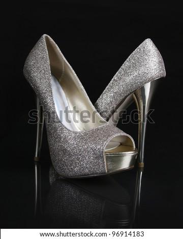 golden glitter shoes on black background - stock photo