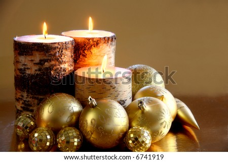 Golden Glow: A trio of candles glows warmly amongst glittering gold ornaments against a reflective gold background. Space for copy. Holiday concept. - stock photo