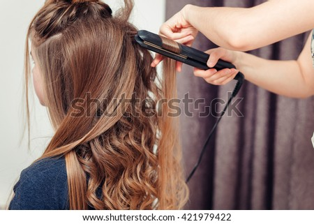 Golden-haired blonde doing the Curling irons in the beauty salon