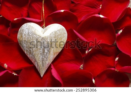Golden heart on red rose petals - stock photo