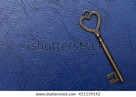 golden heart shaped vintage key on a blue leather background    - stock photo