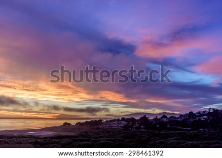 Golden hour, thunderheads, pending storm, painted sky, and reflective sea at sunset, on (Big Sur Coast) Moonstone Beach, with people in the distance. California Central Coast, near Cambria CA. - stock photo