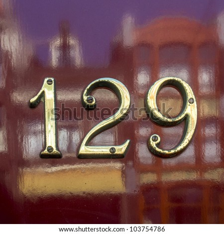 golden house number hundred and twenty-nine, on a red shiny door with the reflection of the opposite houses. - stock photo