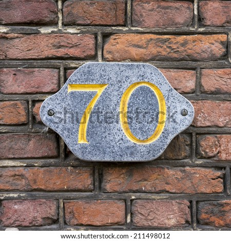 Golden house number seventy, engraved in natural stone - stock photo
