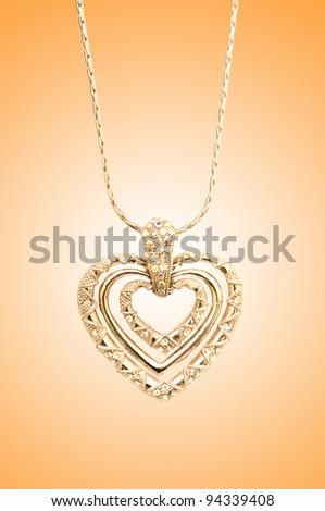 Golden jewellery against gradient background - stock photo
