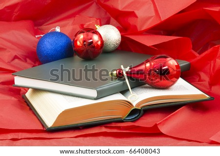 Golden key and open book and closed book on red paper with holiday ornaments reflect the gift that opens knowledge - stock photo