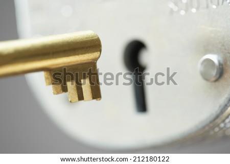 Golden key and padlock, close-up, selective focus - stock photo