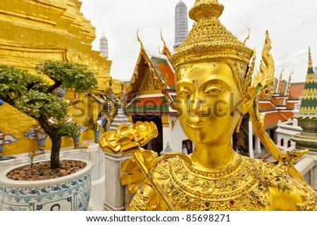 golden kinnara statue in grand palace bangkok - stock photo
