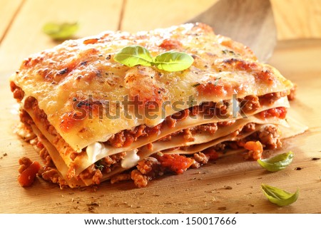 Golden lasagne with meat, tomatoes, cheese sauce and pasta in alternating layers on a wooden board garnished with basil