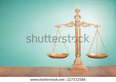 Golden Law scales on table. Symbol of justice - stock photo