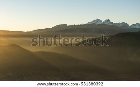 Golden light in the fog in the mountains at sunset