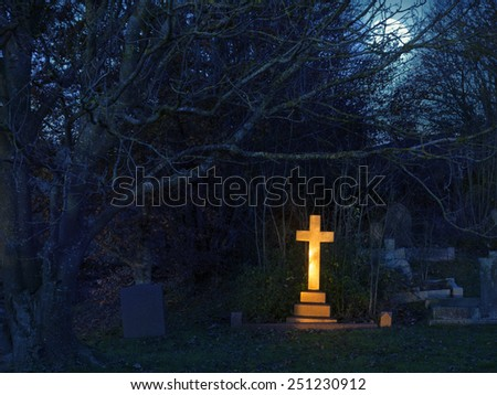 Golden light  shining upon a gravestone cross in a cemetery in England, United Kingdom - stock photo