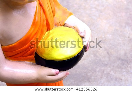 Golden monk 's bowl in hand of statue monk - stock photo