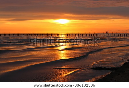 Golden natural sea sunset view of jetty or small bridge at horizon with people  silhouette and orange sky landscape. Sunset or sunrise reflection in nature with sun in clouds above black sea scenery.  - stock photo
