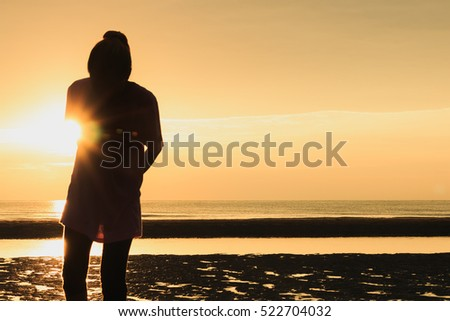 Golden natural sea sunset with girl people silhouette and orange sky landscape.