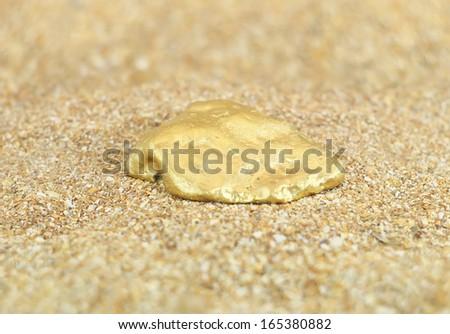 golden nugget treasure in coarse sand - stock photo