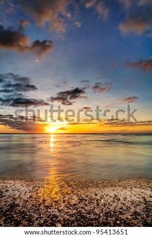 Golden ocean sunset over beach. - stock photo