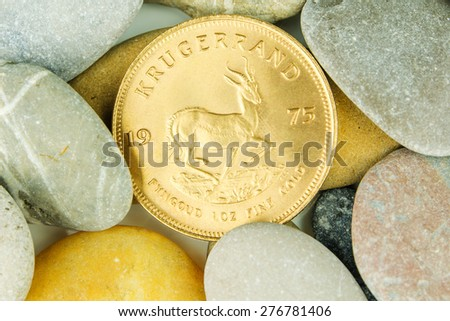 golden ounce of krugerrand coin hidden under pebble stones - stock photo