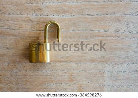 Golden padlock on wood background - stock photo