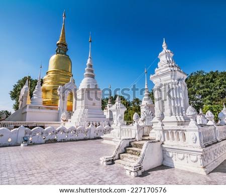 Golden pagoda at Wat Suan Dok (monastery) against a blue sky, Chiangmai, Thailand.  - stock photo
