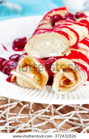 Golden pancakes with cranberry jam, milk glas and honey in a summer style. Top view. Homemade rolled crepes with berries and fruit on a wooden table. Cheese Blintzes, ricotta. delicious breakfast - stock photo