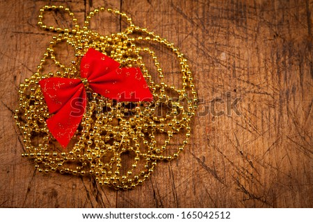 Golden pearl with red bow on rustic wooden background