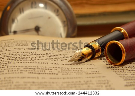 Golden pen on the book - stock photo