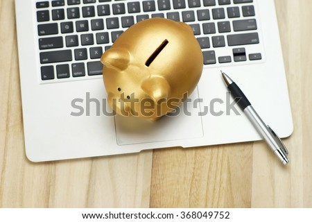 Golden piggy bank and pen on notebook. financial concept - stock photo