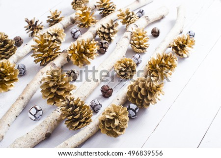 golden pine and cypress cones Christmas decoration with birch branches on white wood table background