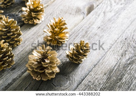 golden pine cones Christmas decoration on old wood table background