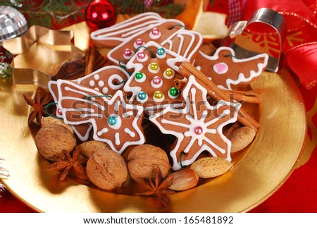 golden plate with gingerbread cookies decorated with icing ,nuts and spices for christmas