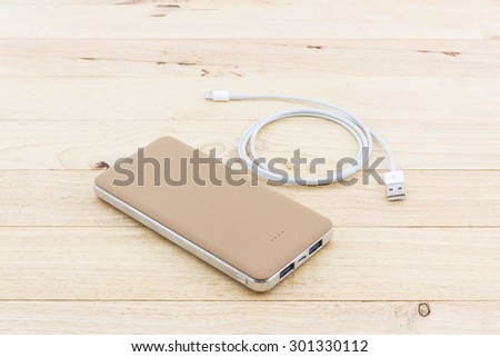 Golden powerbank and USB cable for smartphone on wood background. - stock photo