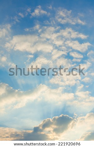 Golden rays of the sun breaking through the clouds - stock photo