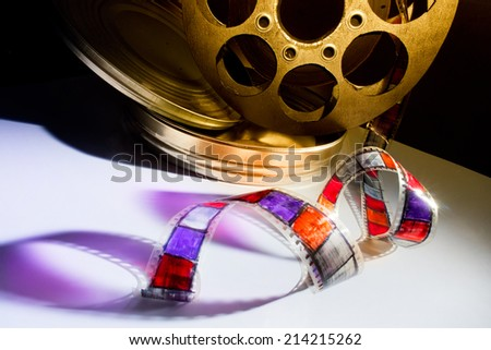 Golden reel of film on a color background - stock photo