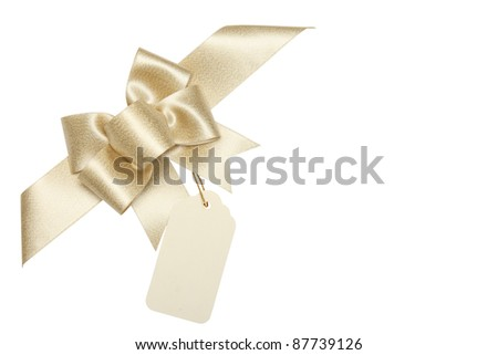 Golden ribbon bow with blank gift tag.Isolated on white.