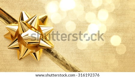 Golden ribbon bow with bokeh,Christmas decoration. - stock photo