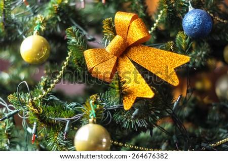 Golden ribbon star hanging at christmas tree  - stock photo