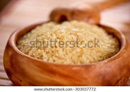 golden rice on wooden plate on wooden background - stock photo