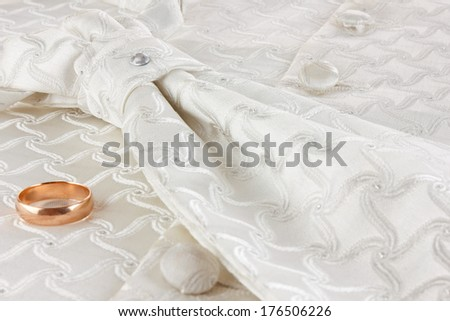 Golden ring and cravat on fabric   background - stock photo