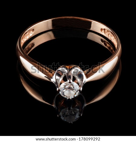 Golden ring with diamond isolated on black background - stock photo