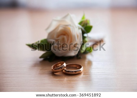 golden rings and wedding boutonniere of white roses on the table, gathering groom - stock photo