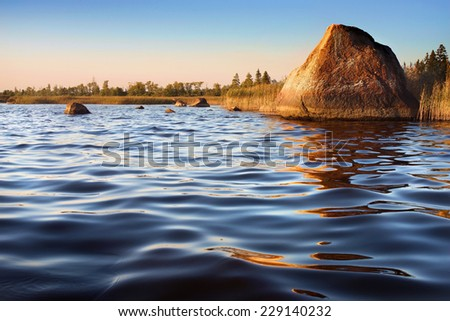 golden rock reflecting in calm water on sunset, Baltic sea