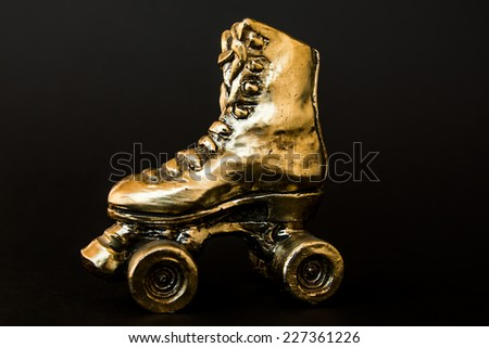 golden roller skate with high heel isolated against black background - stock photo