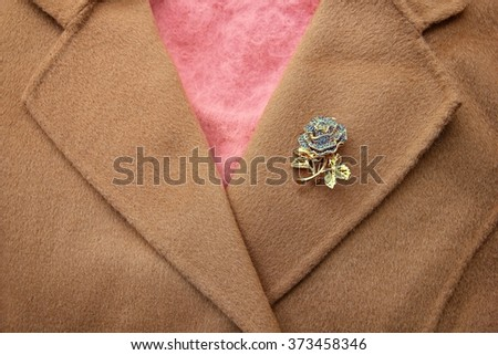 Golden rose brooch on khaki wool coat with pink sweater inside. - stock photo