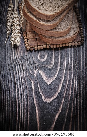 Golden rye wheat ears sliced loaf of bread wicker table mat food and drink concept. - stock photo