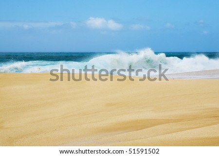 Golden sand and blue surf with a wave crashing along the shore in Hawaii. - stock photo