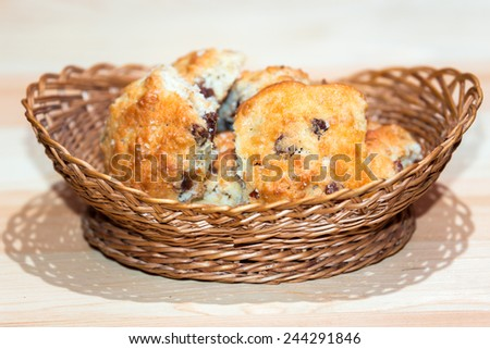 Golden sand cakes with raisin in wicker basket on wooden surface - stock photo