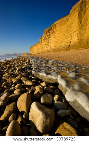 Golden sandstone cliffs at low tide, Burton Bradstock, Dorset, UK
