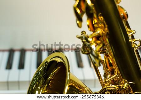 golden saxophone on a white background piano - stock photo