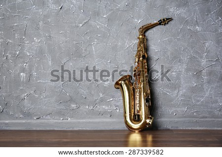 Golden saxophone on gray wall background